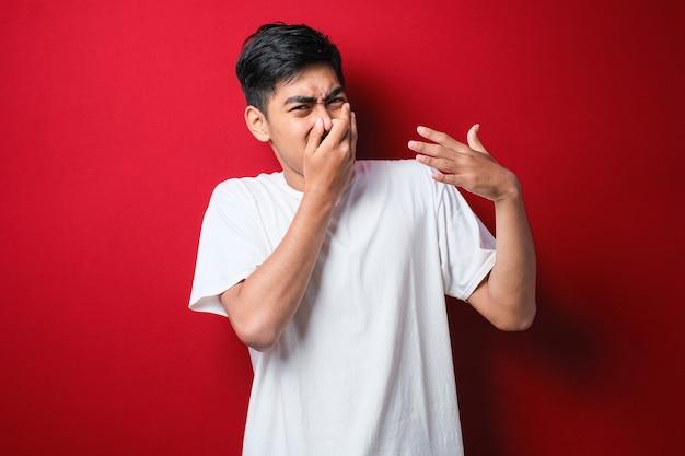 赤い背景の上に白いtシャツを着た若いアジア人男性は、臭い、嫌な、耐え難い匂いを嗅ぎ、鼻に指で息を止めます。悪臭