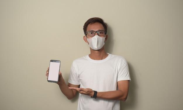 흰색 티셔츠와 의료용 마스크를 쓴 젊은 아시아 남성은 빈 흰색 스마트폰 화면을 보여줍니다.