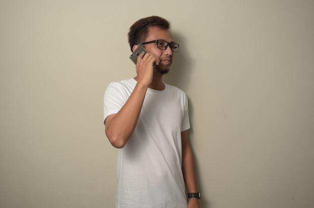 전화로 말하는 얼굴에 미소와 함께 서있는 흰색 티셔츠를 입고 젊은 아시아 남자