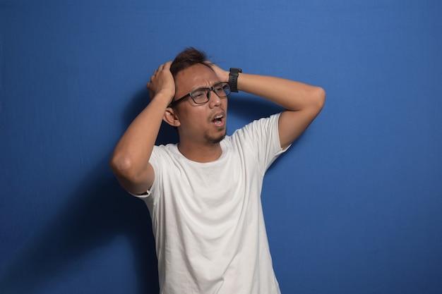 片頭痛に苦しんでいるストレスのために頭の頭痛に手で白いtシャツを着ている若いアジア人男性