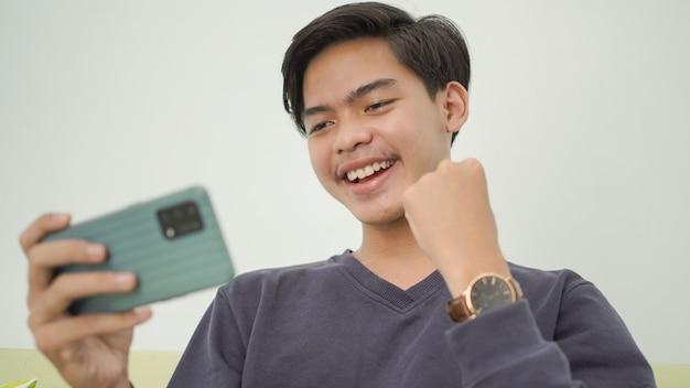 젊은 아시아 남자가 집에서 그의 게임에서 승리