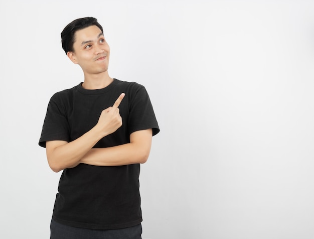Young asian man with black shirt pointing to the side with a finger to present a product or an idea while looking forward surprising isolated