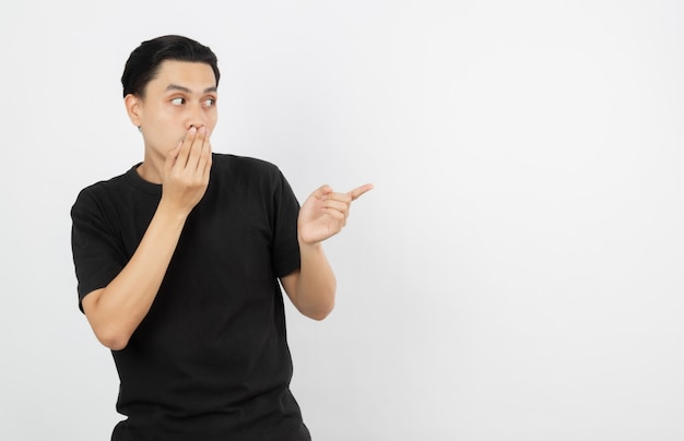 Young asian man with black shirt pointing to the side with a finger to present a product or an idea while looking forward surprising