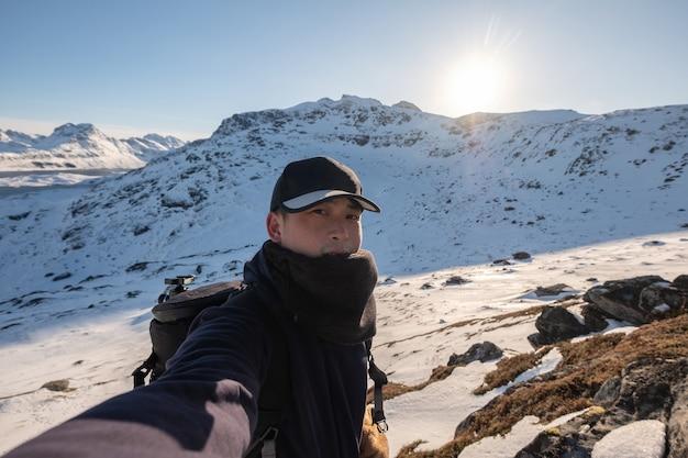Молодой азиатский мужчина в кепке делает селфи на камеру во время прогулки по заснеженной горе в норвегии