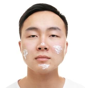 白い背景の上の顔に適用された問題の肌のためのクリームと若いアジア人男性