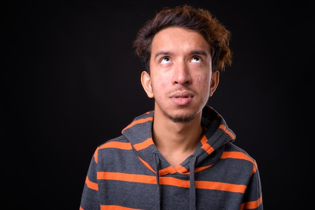 Young asian man with curly hair and acne wearing hoodie against black space