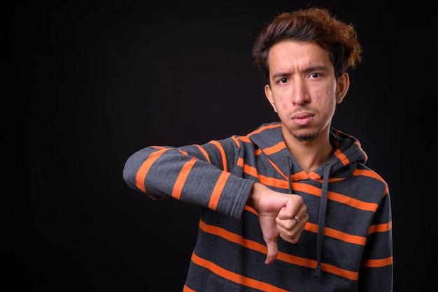 黒いスペースに対してパーカーを着て巻き毛とにきびを持つ若いアジア人男性
