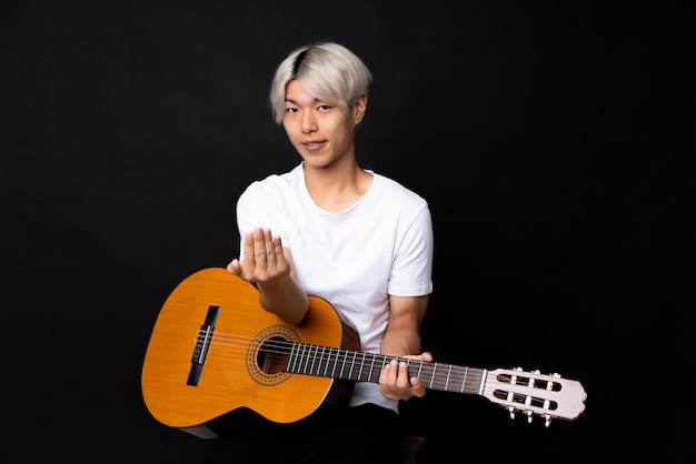 Young asian man with guitar over black inviting to come with hand, happy that you came