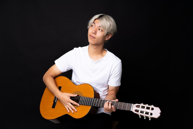 Young asian man with guitar over black making doubts gesture while lifting the shoulders