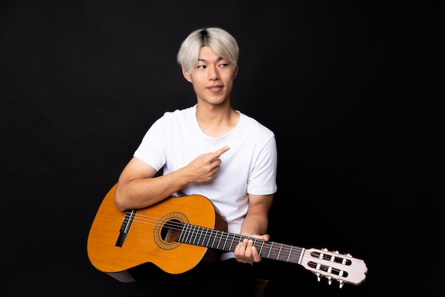 Young asian man with guitar over black pointing to the side to present a product