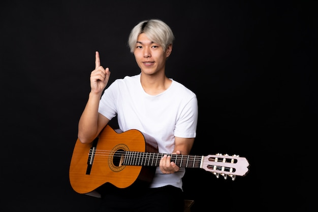 Young asian man with guitar over black pointing up a great idea