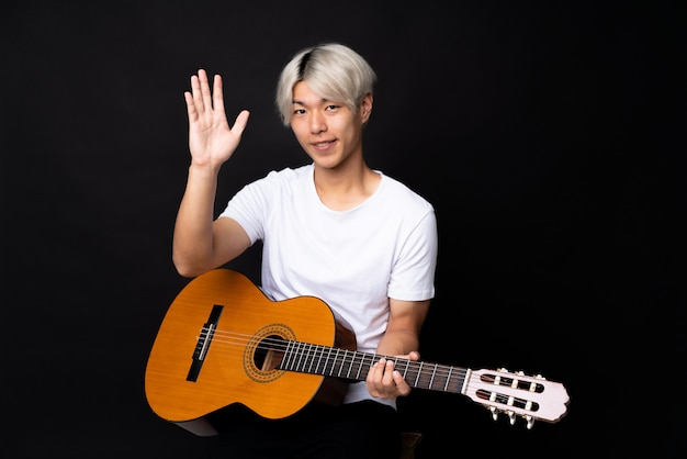 Young asian man with guitar over black saluting with hand with happy expression