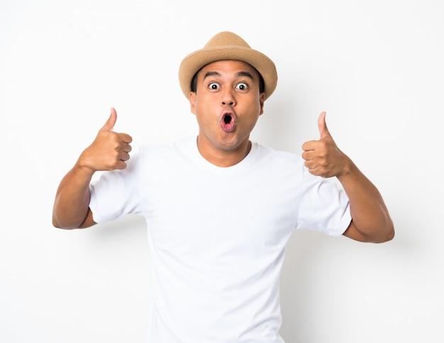 帽子を持つ若いアジア人は、過度の表情でショックと驚きを感じています。