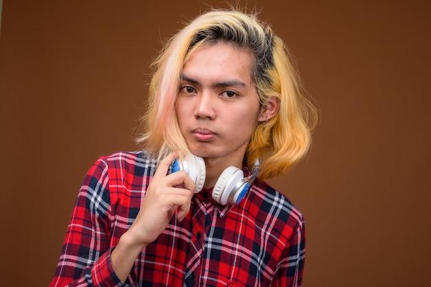 茶色の背景にスタイリッシュな服を着ているヘッドフォンで若いアジア男