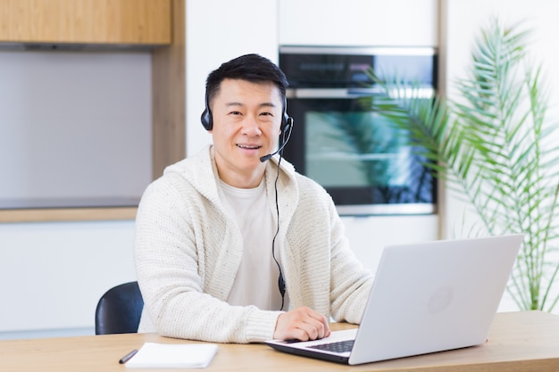 Young asian man with headset looks at camera and smiles sitting at home laptop