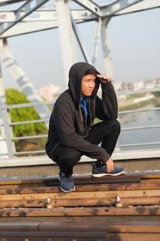 Giovane uomo asiatico con giacca con cappuccio accovacciato su una ferrovia che guarda lontano con la mano sulla fronte