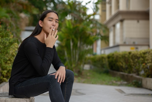 Young asian man with long hair sitting and smoking at the park