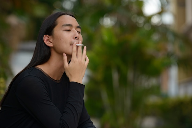 Young asian man with long hair smoking at the park