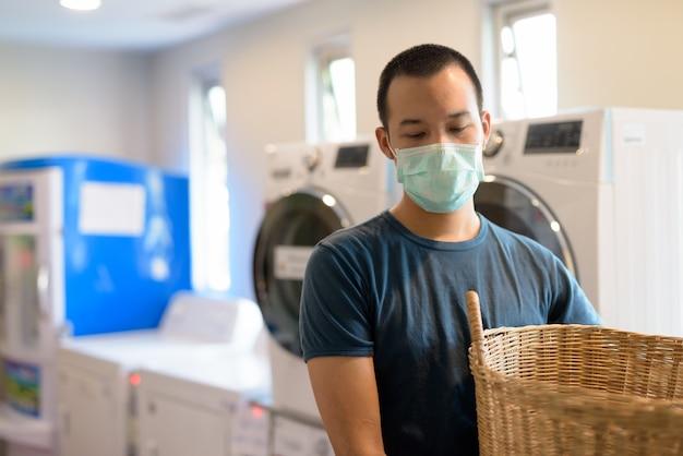コインランドリーの洗濯でコロナウイルスの発生から保護するためのマスクを持つ若いアジア人