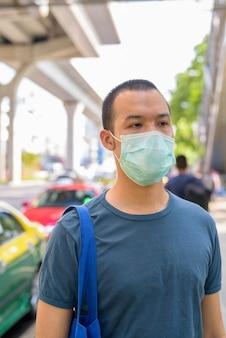 市内のタクシー乗り場でのコロナウイルスの発生からの保護のためのマスクを持つ若いアジア人