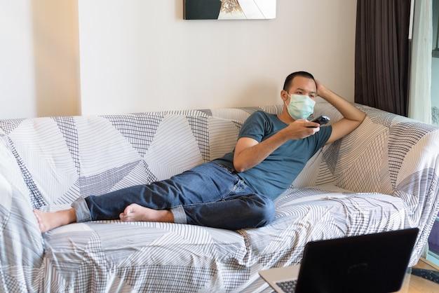 ソファーで横になっていると、検疫の下で自宅でテレビを見てマスクを持つ若いアジア男