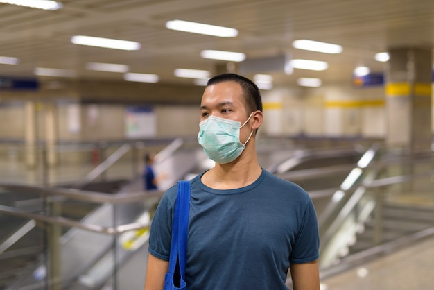 Young asian man with mask for protection from coronavirus outbreak at the subway station