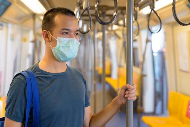 Молодой азиатский мужчина с маской, стоящий на расстоянии внутри поезда