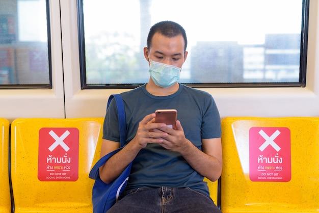 Молодой азиатский мужчина с маской, используя телефон и сидя на расстоянии внутри поезда