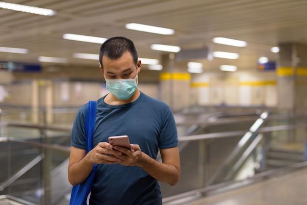 Молодой азиатский мужчина с маской, используя телефон на станции метро