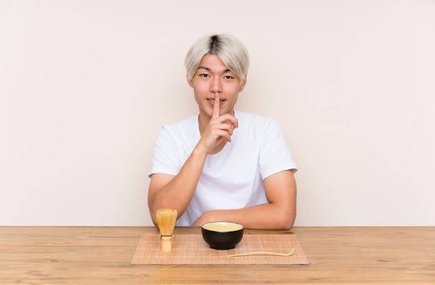 침묵 제스처를 하 고 테이블에 말 차 젊은 아시아 남자