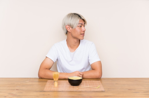 Young asian man with matcha tea in a table looking to the side