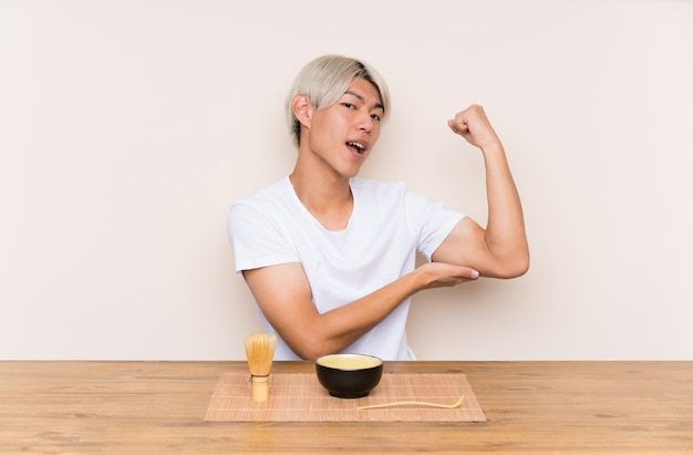 Young asian man with matcha tea in a table making strong gesture