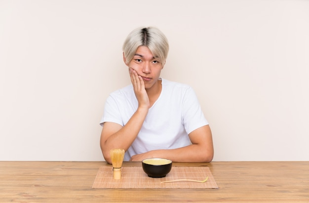 Young asian man with matcha tea in a table unhappy and frustrated