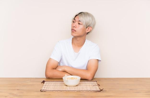 Молодой азиатский человек с рамэнами в таблице смотря сторону