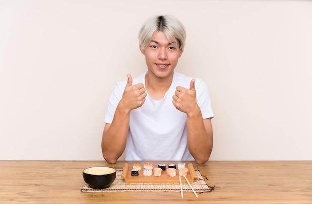 엄지 손가락 제스처를주는 테이블에 초밥과 젊은 아시아 사람