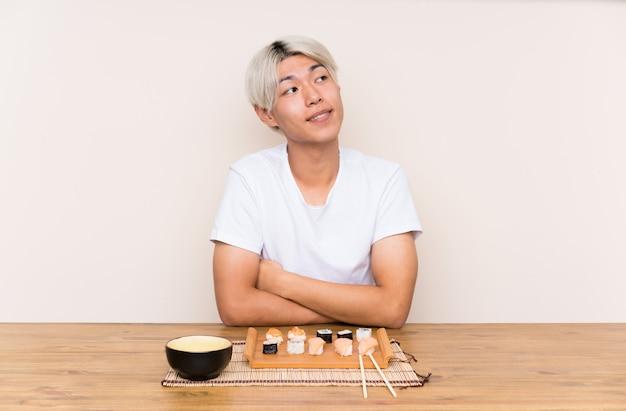 웃으면 서 찾고 테이블에 초밥과 젊은 아시아 남자
