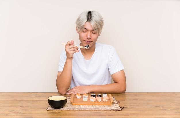 테이블에 초밥과 젊은 아시아 남자