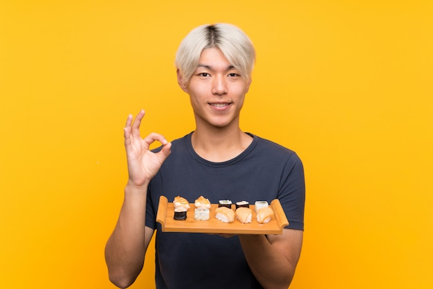 Young asian man with sushi over isolated yellow showing an ok sign with fingers