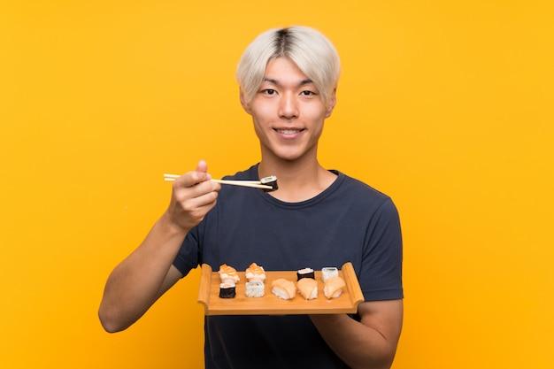 고립 된 노란색 이상 초밥으로 젊은 아시아 남자