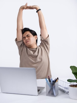 オフィスで働いている若いアジア人男性、彼はリラックスのために自分自身を伸ばしたり、怠惰にしています。白い背景で隔離のスタジオショット。