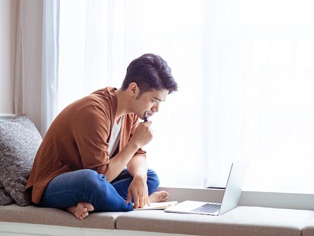 노트북에 글을 쓰고 노트북을 사용하는 젊은 아시아 남자.
