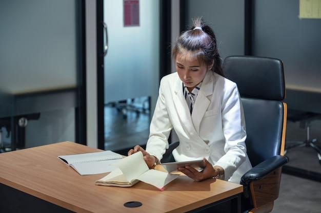 젊은 아시아 관리자 여자 읽기 및 사무실에서 책상에 태블릿 노트북을 확인