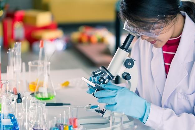젊은 아시아 의료 기술자 여성 과학 실험실에서 연구를하는 동안 테스트 튜브로 테스트를합니다.