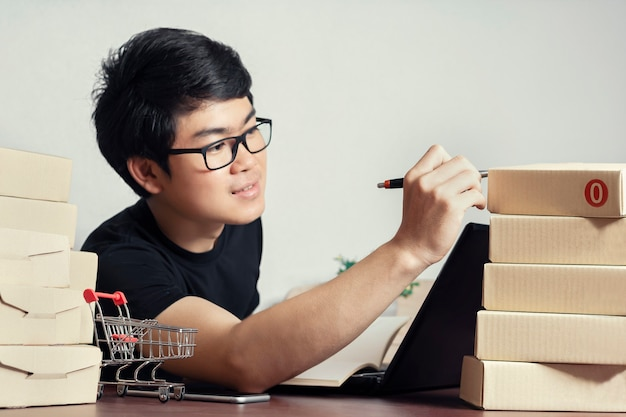 若いアジア人男性カジュアルスタイル、起業家在庫品や梱包箱をチェック