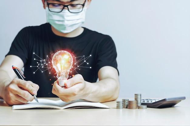 自宅で仕事をしているマスクに電球を持っている若いアジア人男性新しい創造的なアイデアのコンセプト