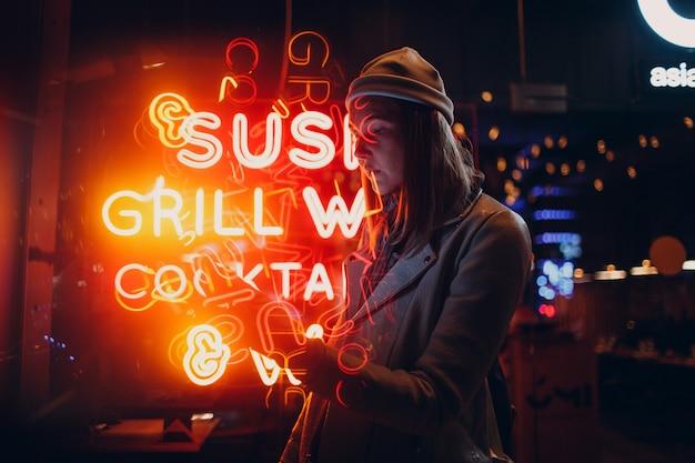 네온 빛 글자 간판에 거리 스타일 패션에 젊은 아시아 밀레 니얼 여자