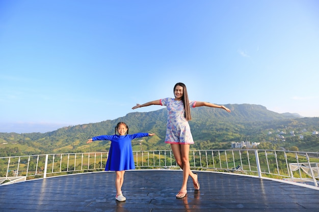 Young asian mom and daughter feeling free with arms wide open at beautiful trees and mountains on blue sky.