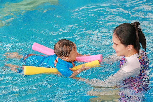 Young asian mom teaching baby boy in swimming pool with noodle foam.