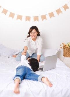 어린 아시아 엄마가 집에서 바닥에 앉아 있는 동안 일하고 있습니다.