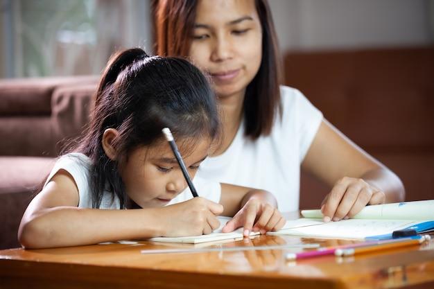 그녀의 딸 집에서 그녀의 숙제를 돕는 젊은 아시아 어머니. 가정 개념에서 교육.